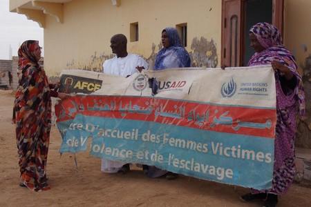 Aminetou Ely et des collaborateurs de l'Association des femmes chefs de famille, déployant à Dar Naïm une banderole du « Centre d'accueil des Femmes Victimes de Violence et de l'esclavage ». Novembre 2016. © 2016 Marie Foray